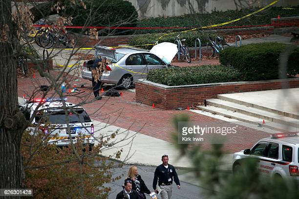 Police investigate the scene where an individual used a car to crash into a group of students outside of Watts Hall on the Ohio State University...