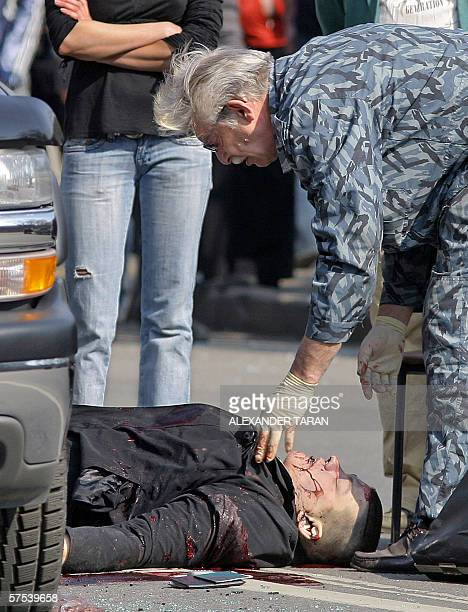A police investigator inspects the body of a bodyguard of the chief of StPetersburg oil terminal stockcompany Sergei Vasiliev following an armed...