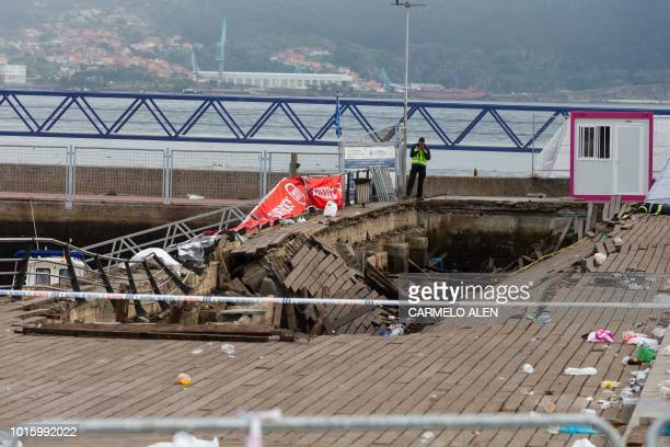 TOPSHOT A police investigator inspects the seafront platform in Vigo on August 13 2018 after a section of a wooden promenade suddenly collapsed with...