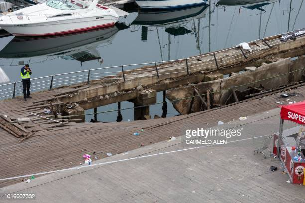 A police investigator inspects the seafront platform in Vigo on August 13 2018 after a section of a wooden promenade suddenly collapsed with people...