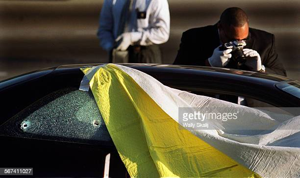 Police investigator photographs the crime scene where a person was shot to death on the westbound 91 Freeway near Wilmington Ave. In Compton.