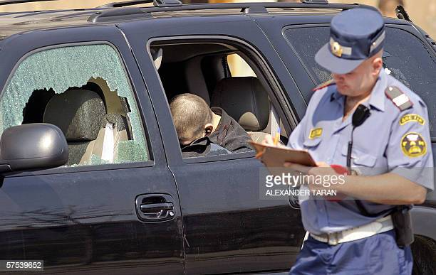 A police investigator takes notes next to an escort car with the body of a bodyguard of the chief of StPetersburg oil terminal stockcompany Sergei...