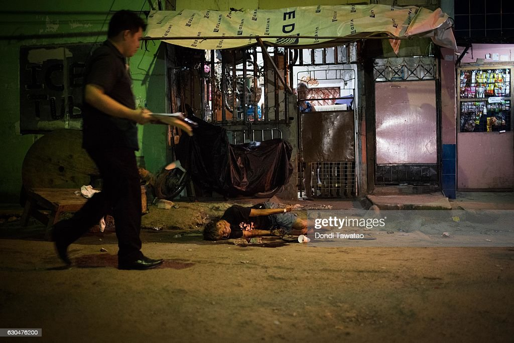 A police investigator walk past a dead body said to be a victim of two motorcycle riding gunmen on December 23, 2016 in Manila, Philippines. Philippine president Rodrigo Duterte has said he wanted the Constitution amended to allow Philippine leaders to wield martial law powers without judicial and congressional approval, a move he said is necessary to contain the ongoing 'drug menace' and maintain peace and security in the country. Around 5,882 people have been killed across the country since President Rodrigo Duterte launched his war on illegal drugs five months ago, according to figures from the Philippine National Police. An average of 25 victims were killed daily during the five-month period, and police kill 97 percent of those they shoot, leaving 33 dead for every person wounded according to the figures. Last October, Duterte himself said the country could expect about 20,000 or 30,000 more deaths in his administration's bloody war on drugs.