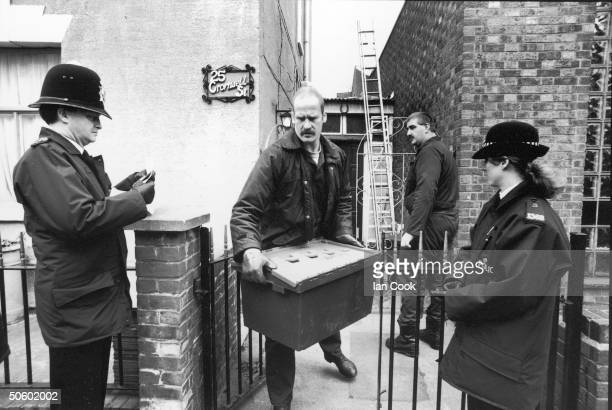 A police investigator walks past a pair of uniformed officers as he carries a large plastic box of evidence from the home of Fred and Rose West at 25...