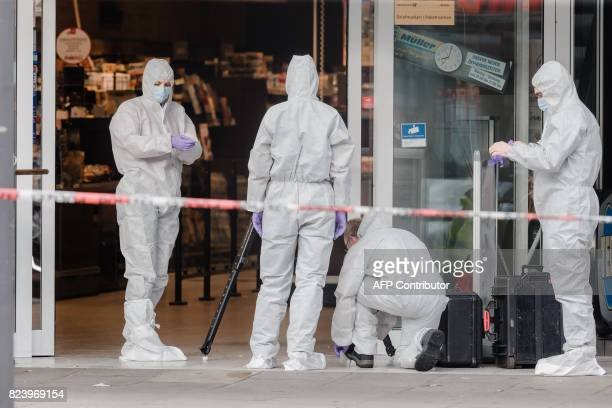 Police investigator work at the area around a supermarket in the northern German city of Hamburg where a man killed one person and wounded several...