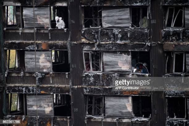 Police investigators are seen inside the burned out shell of Grenfell Tower in London on October 17 2017 as investigations continue into the tragedy...