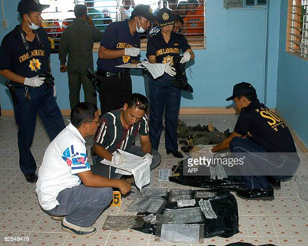 Police investigators check recovered items from a crashed Philippine Air Force C130 cargo plane in Davao on the southern island of Mindanao on August...