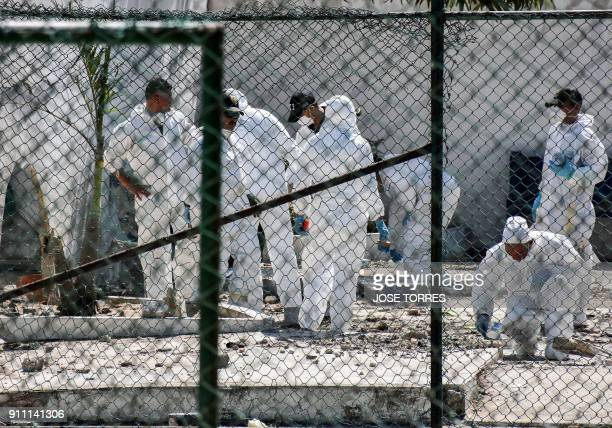 Police investigators check the site where a bomb exploded in Barranquilla Colombia on January 27 2018 At least three police officers were killed...