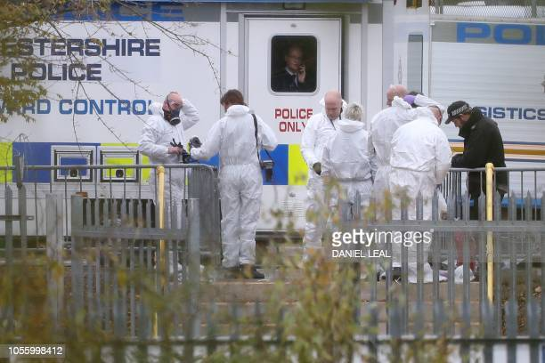 Police investigators in forensics suits work at the helicopter crash site outside Leicester City Football Club's King Power Stadium in Leicester...