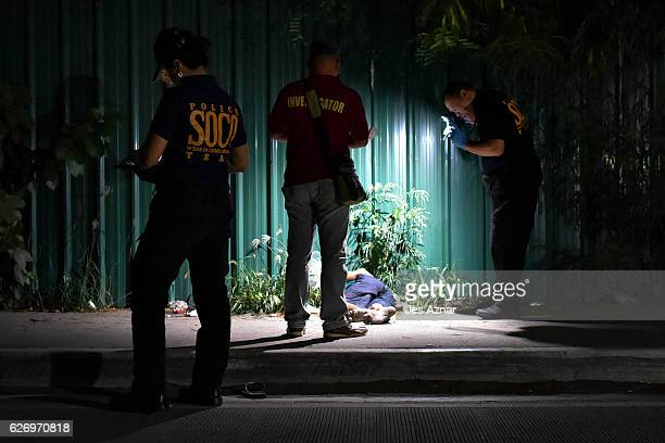 Police investigators inspect a crime scene where two still unidentified men are bound and wrapped in packaging tape were left in a dark streeton...