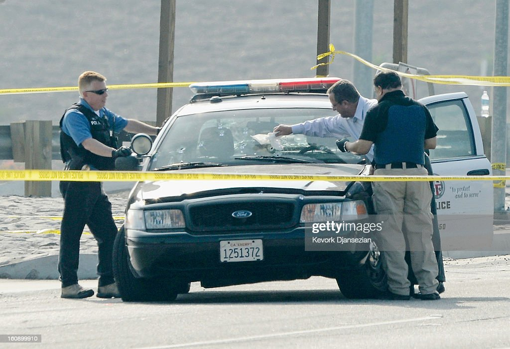 Police investigators inspect bullet riddled Los Angeles Police Department squad car where a police officer was shot on Magnolia Ave. over the Interstate 15 Freeway on February 7, 2013 in Corona, California. Former Los Angeles police officer Christopher Jordan Dorner, 33, who had allegedly warned he would target law enforcement, is suspected of firing on two LAPD officers and ambushing two other officers, killing one. Dorner is also a suspect in two weekend killings of Monica Quan and Keith Lawrence who were found dead in a car inside a parking structure.