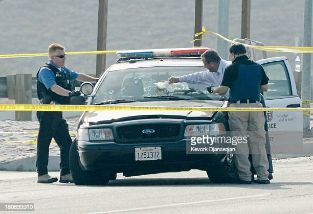 Police investigators inspect bullet riddled Los Angeles Police Department squad car where a police officer was shot on Magnolia Ave over the...