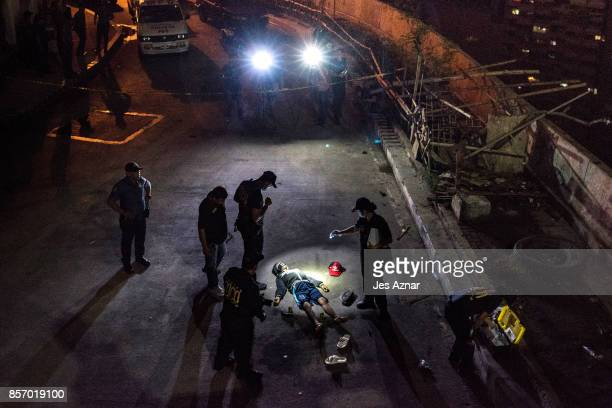 Police investigators inspect the body of John Estrella who was allegedly killed by unidentified assailants on June 26 2017 in Manila Philippines As...