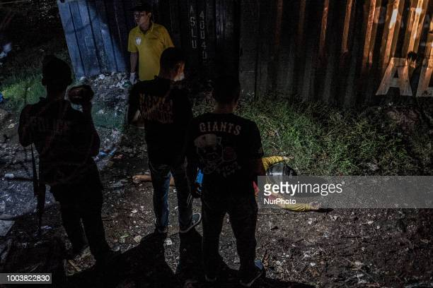 Police investigators inspect the body of one of two suspected drug dealers who were killed by police during a drug sting operation in Manila...