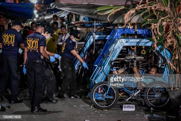 Police investigators inspect the scene where Mateo Gravillo a former drug user according to a relative was killed by unknown attackers in Manila...