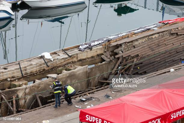 Police investigators inspect the seafront platform in Vigo on August 13 2018 after a section of a wooden promenade suddenly collapsed with people...