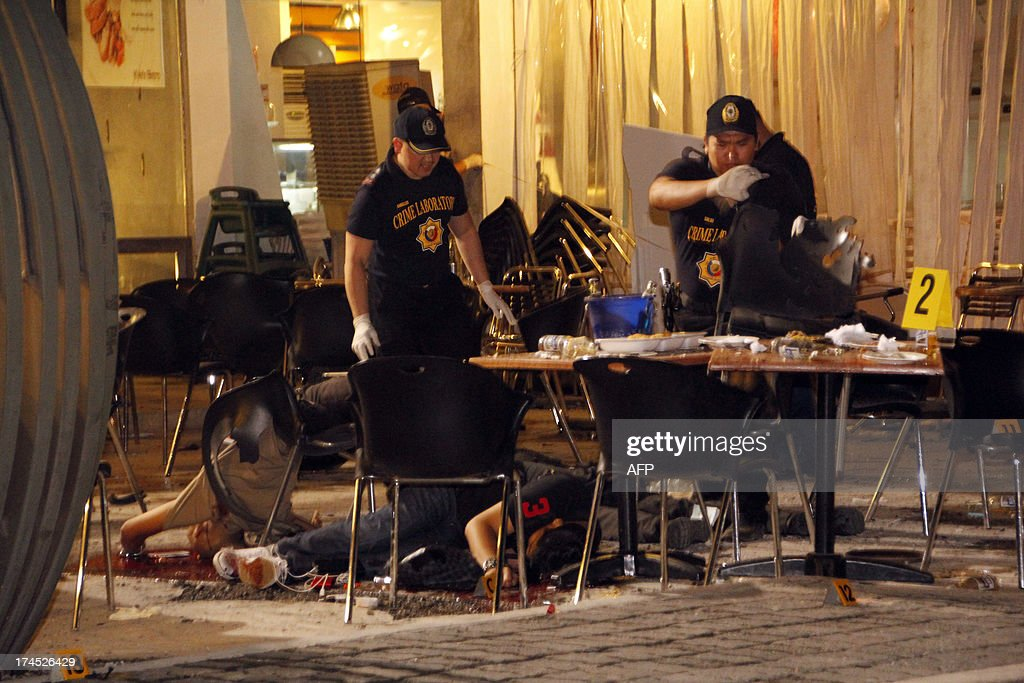 Police investigators look for evidence amongst the ruins and dead bodies of victims after an improvised explosive device went off at a popular restaurant in Cagayan de Oro City, on the southern island of Mindanao on July 26, 2013. Six people were killed and more than 40 wounded in the Philippines when a bomb struck a restaurant filled with doctors after a national convention, police said on July 27. AFP PHOTO/ JB Deveza