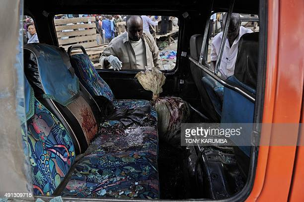 Police investigators look into a damaged public transport vehicle at the scene of an explosion on May 16 2014 on the outskirts of Nairobi's business...