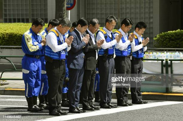 Police investigators observe a moment of silence ahead of a recreation of the circumstances of a fatal car accident in Tokyo's Ikebukuro district on...
