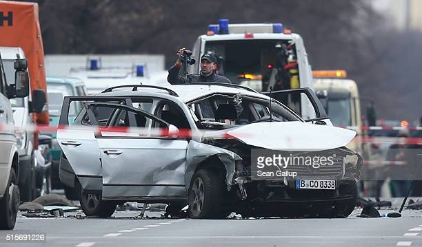 Police investigators stand next to a car destroyed by a bomb that killed the driver in the city center on March 15 2016 in Berlin Germany According...