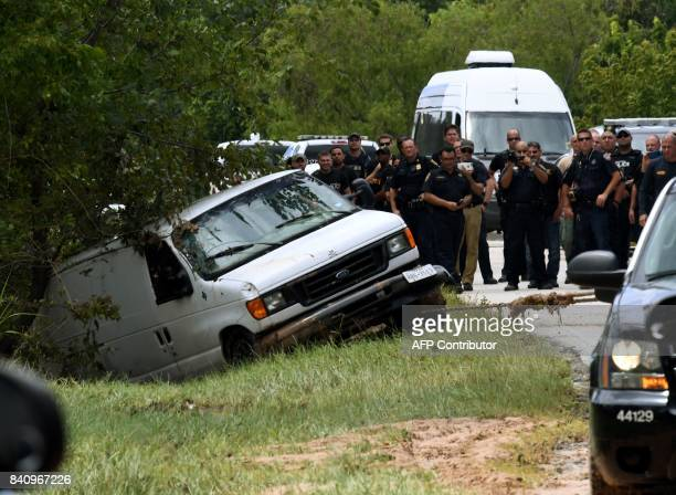 Police investigators watch as the van containing the six members of the the Saldivar family who died is towed to the road after they crashed their...