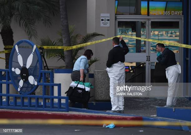 Police investigators work at the Gable House Bowl center after 3 men were killed and 4 injured in a shooting at the bowling alley in Torrance...