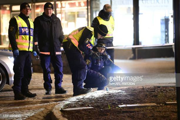 """Police investigators work at the scene where a man attacked eight people with a """"sharp weapon,"""" seriously injuring two, in the Swedish city of..."""