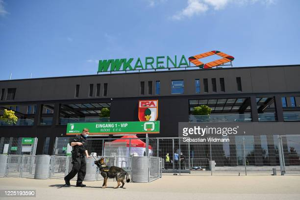 Police is seen outside the stadium with a guard dog outside the WWK-Arena ahead of the Bundesliga match between FC Augsberg and VFL Wolfsburg takes...