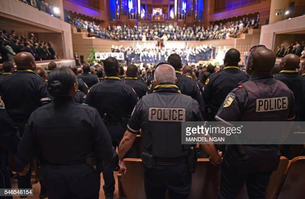 Police join hands during the singing of The Battle Hymn of the Republic during an interfaith memorial service for the victims of the Dallas police...
