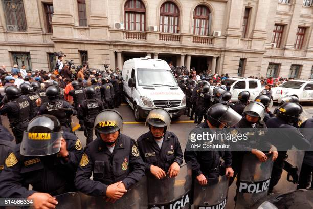 Police keep a security perimeter as the vehicle transporting former Peruvian President Ollanta Humala and his wife Nadine Heredia to the place where...