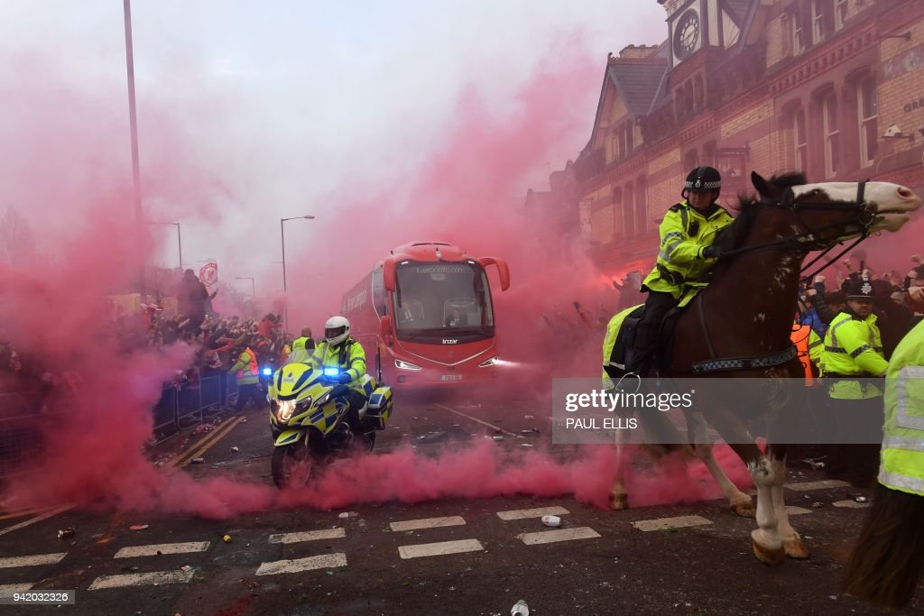 TOPSHOT - Police keep control as Liverpool players arrive by bus through smoke and beercans before the UEFA Champions League first leg quarter-final football match between Liverpool and Manchester City, at Anfield stadium in Liverpool, north west England on April 4, 2018. / AFP PHOTO / Paul ELLIS