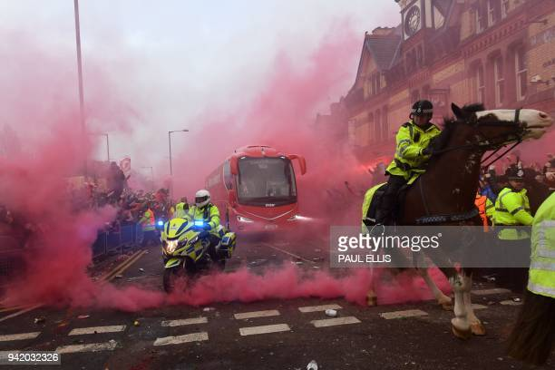 TOPSHOT Police keep control as Liverpool players arrive by bus through smoke and beercans before the UEFA Champions League first leg quarterfinal...