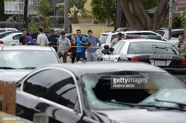Police keep onlookers away from the scene where a car allegedly driven by a gunman crashed, on May 24, 2014 in Isla Vista, California, a beach...
