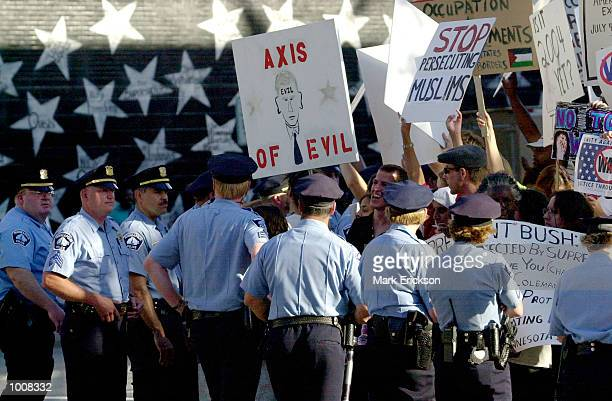 Police keep protesters at bay near the the Target Center where US President George W Bush was attending a Republican fundraiser July 11 2002 in...