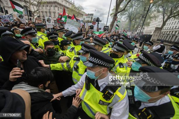 Police keep the crowd away from a small group of pro-Israel demonstrators as thousands of people attend a protest and block Whitehall to demonstrate...