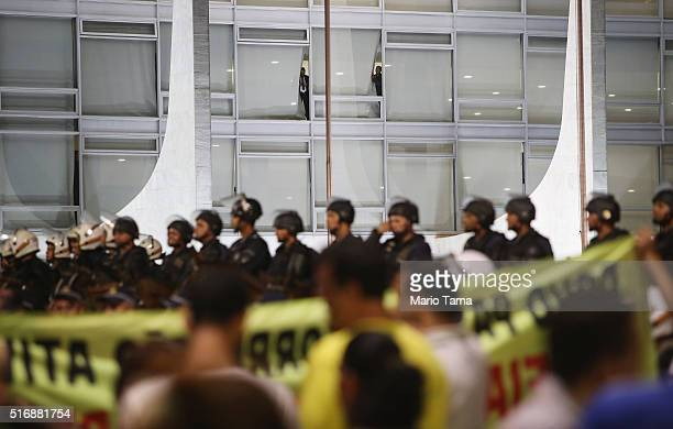 Police keep watch as antigovernment protestors gather outside the Planalto presidential palace on March 21 2016 in Brasilia Brazil Protestors rallied...