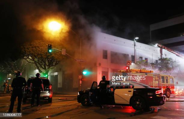 Police keep watch as firefighters work to extinguish a fire at a section of shops looted amid demonstrations in the aftermath of George Floyd's death...