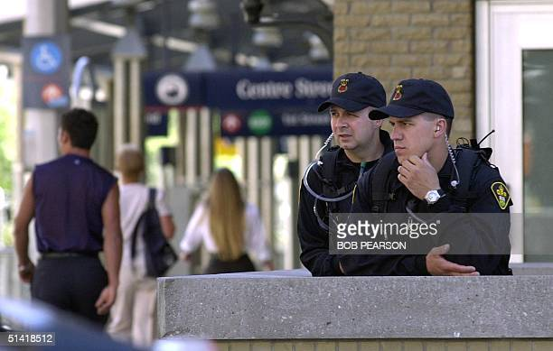 Police keep watch on a street corner near the G8 International Media Center 25 June 2002 in Calgary Alberta Canada prior to the start of the G8...