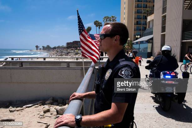Police keep watch over the less restricted beachfront over Memorial Day weekend May 24, 2020 in Ventura, California. Officials said people for the...