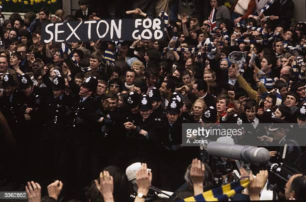Police keeping back crowds of Chelsea Football Club supporters as they strain for a glimpse of manager Dave Sexton A banner in the crowd reads...