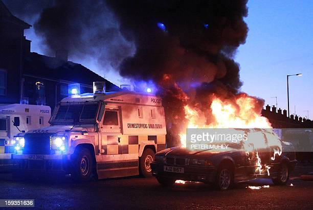 Police landrovers take up positions around a burning car during violence between loyalists nationalists and the police in east Belfast Northern...