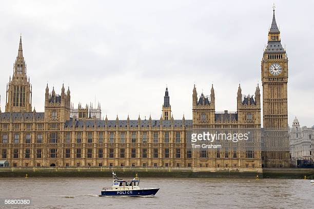 Police launch passes The Houses of Parliament Westminster River Thames London UK