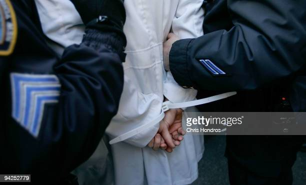Police lead a doctor and health care activist who was blocking the front door of the building where Sen Chuck Schumer's office is located to a...