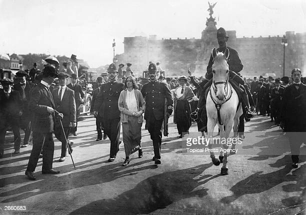 Police lead away a few Suffragettes, arrested for chaining themselves to the railings of Buckingham Palace, to draw attention to their cause.