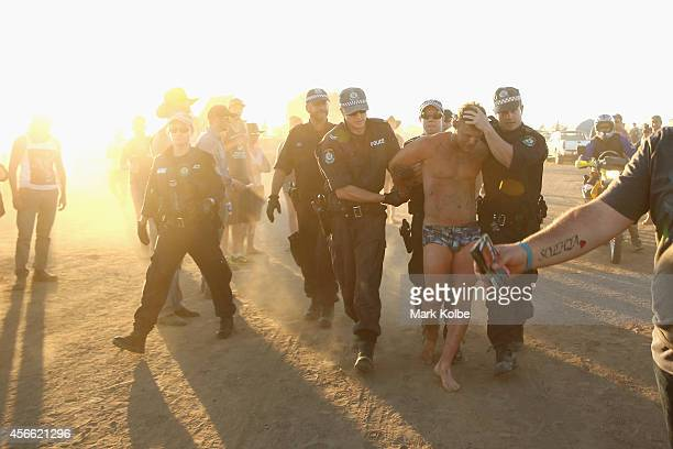 Police lead away a man after an altercation in the 'Ute Paddock' on the second day of the 2014 Deni Ute Muster at the Play on the Plains Festival...