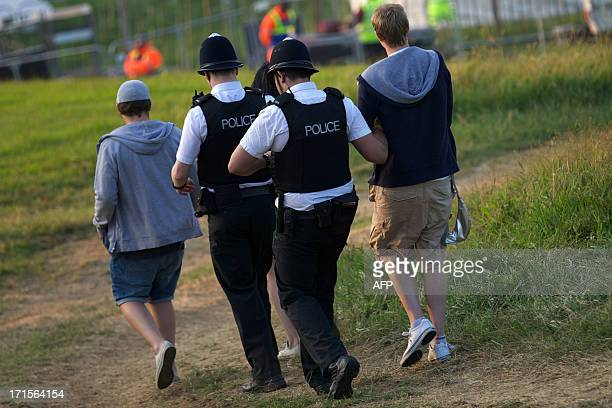 Police lead away a man on the first day of the Glastonbury Festival of Contemporary Performing Arts near Glastonbury southwest England on June 26...