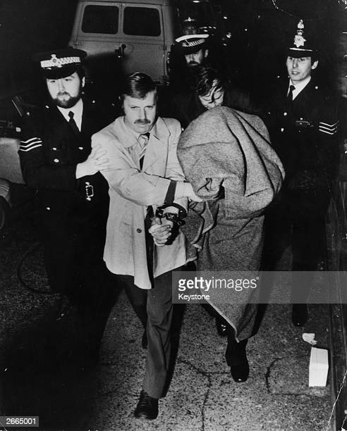 Police leading murderer Peter Sutcliffe, known as the Yorkshire Ripper, into Dewsbury Court under a blanket.