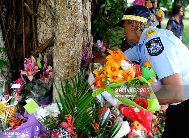 A police liason officer places flowers at a make shift memorial in a park next to the home of a multiple stabbing in the suburb of Manoora on...