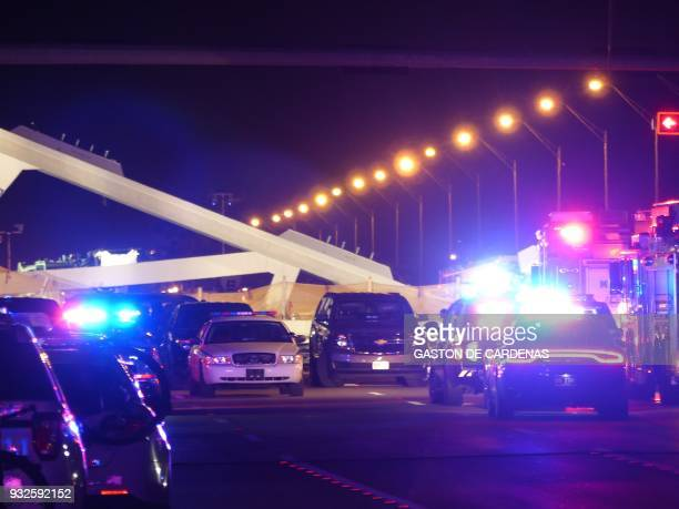 Police lights illuminate the scene of a pedestrian bridge collapse in Miami Florida on March 15 crushing a number of cars below and reportedly...