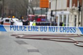 Police Line Do Not Cross tape against blurred city background